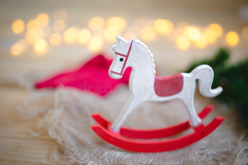 Closeup of beautiful New Year tree decorations, wooden horse against the background of Christmas lights royalty free stock photography