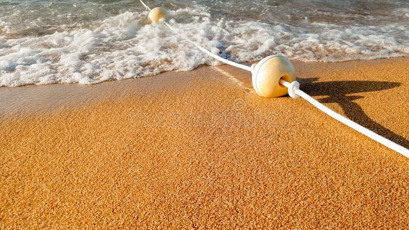Closeup beautiful image of long line of floating buoys connected by rope floating in sea and lying on sandy beach. Closeup beautiful photo of long line of royalty free stock photo