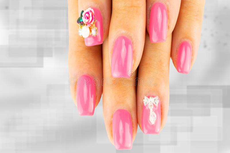 Closeup of beautiful pink nail design at female fingers on brigh. T gray background. Two figure on the nails decorate the pink nail design. Fashion nail design stock photo