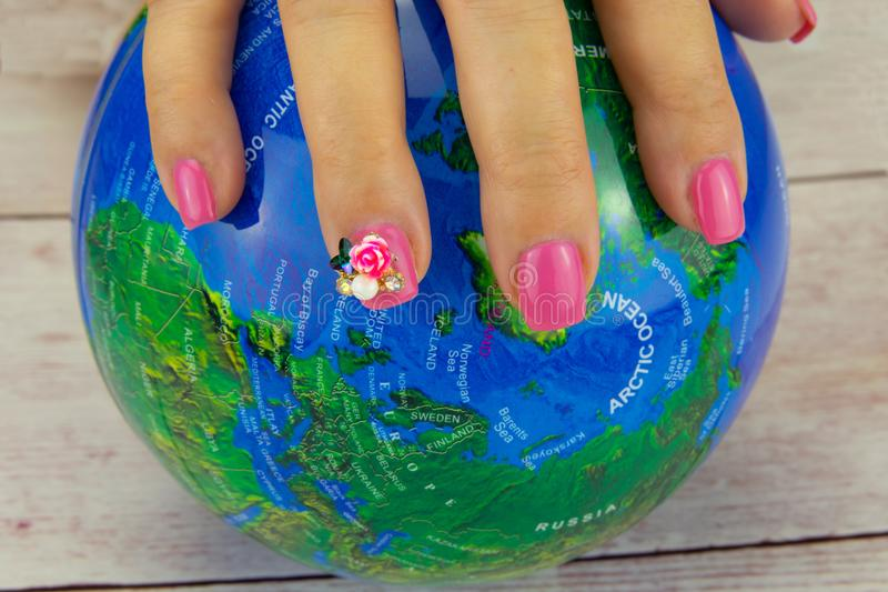 Closeup of beautiful pink nail design at female hand at earth on royalty free stock images