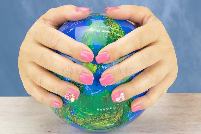Closeup of beautiful pink nail design at female hands at globe o royalty free stock photo