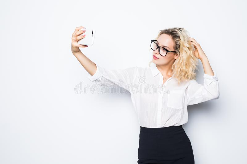 Portrait of young business woman making selfie photo on isolated white background royalty free stock photos