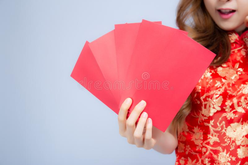 Closeup beautiful portrait young asian woman cheongsam dress smiling holding red envelope on white background. Girl celebrate with exciting, happy Chinese New royalty free stock photos