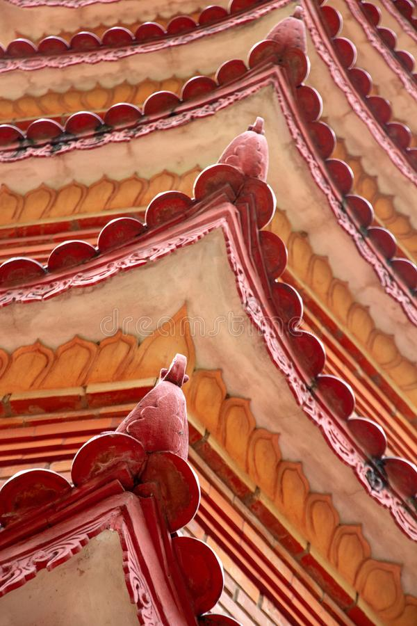 Closeup of roofline architectural details of the Tran Quoc Pagoda, Hanoi, Vietnam. Closeup of the beautiful red and orange repeating roofline of the iconic Tran stock photo