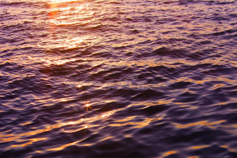Closeup beautiful shot of body of water with the sun reflecting on it at sunset. A closeup beautiful shot of body of water with the sun reflecting on it at stock image