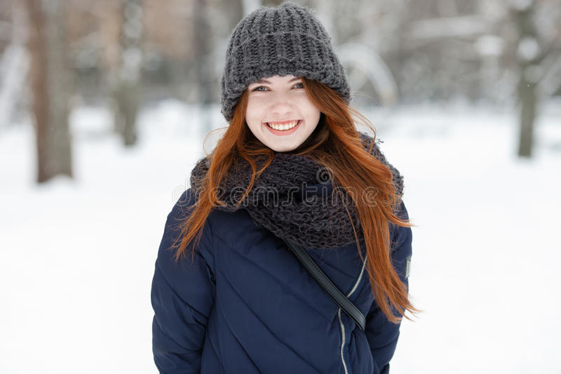 Closeup beautiful winter portrait of young adorable smiling redhead woman in cute knitted hat winter snowy park stock photos