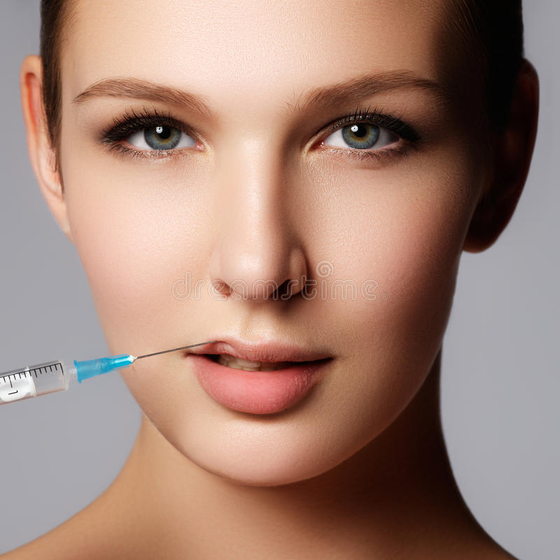 Closeup of beautiful woman gets injection in her lips. Full lips. Beautiful face and the syringe (plastic surgery and cosmetic injection concept stock photos