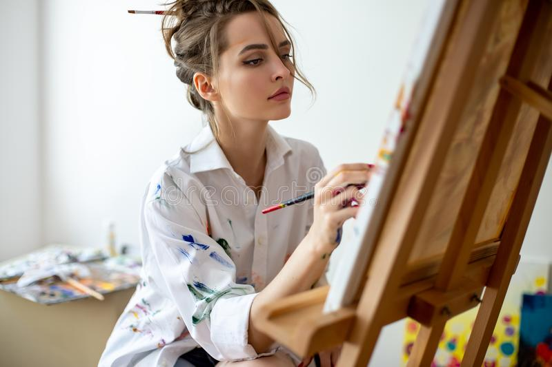 Closeup of beautiful woman painting on canvas in studio. Creative concept stock image