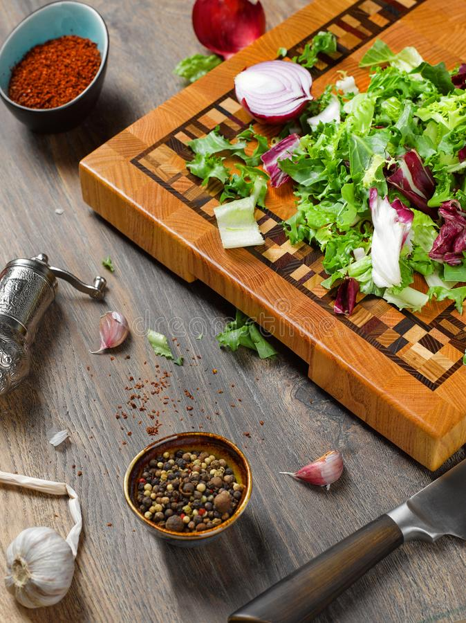 Closeup of a beautiful wooden cutting board with a knife on a wooden background. With salad, onion, spices and garlic. The concept of vegetarian food royalty free stock image