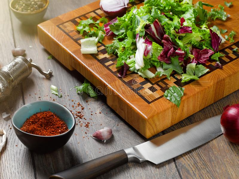 Closeup of a beautiful wooden cutting board with a knife. On a wooden background with salad, onion, spices and garlic. The concept of vegetarian food stock photo