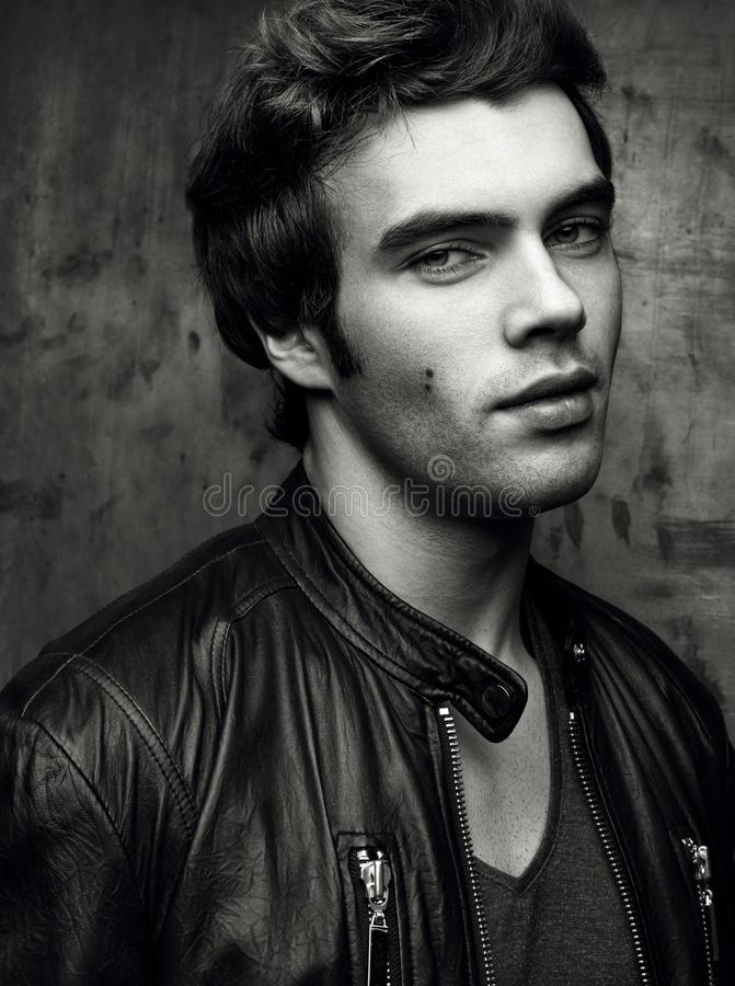 Closeup of a beautiful young man in black leather jacket. Contrast black stock image