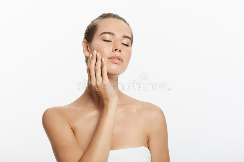 Closeup beauty model girl face with natural nude makeup and clean skin. Skincare facial treatment concept. White stock images