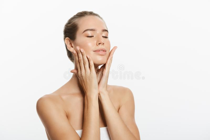 Closeup beauty model girl face with natural nude makeup and clean skin. Skincare facial treatment concept. White. Background royalty free stock image
