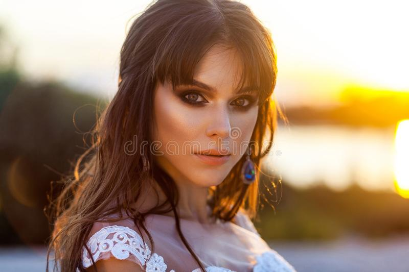 Closeup beauty portrait of beautiful calm brunette woman with makeup and hairstyle wearing white wedding dress on blurred sunset stock photos