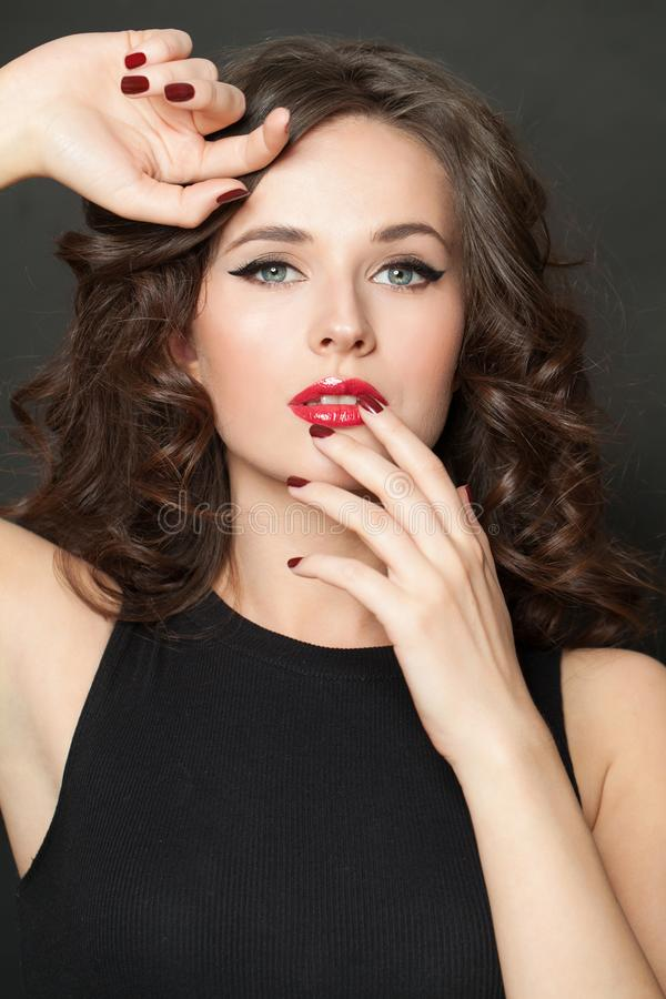 Closeup beauty portrait of beautiful fashion woman brunette with makeup, curly hair and red manicured nails stock images