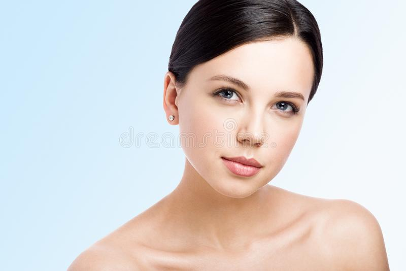 Closeup beauty portrait of beautiful young woman with perfect clean skin. Isolated on blue stock photography