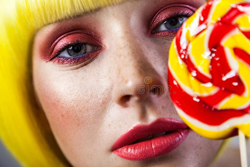 Closeup beauty portrait of calm cute young female model with freckles, red makeup and yellow wig, holding colorful candy stick and stock photo