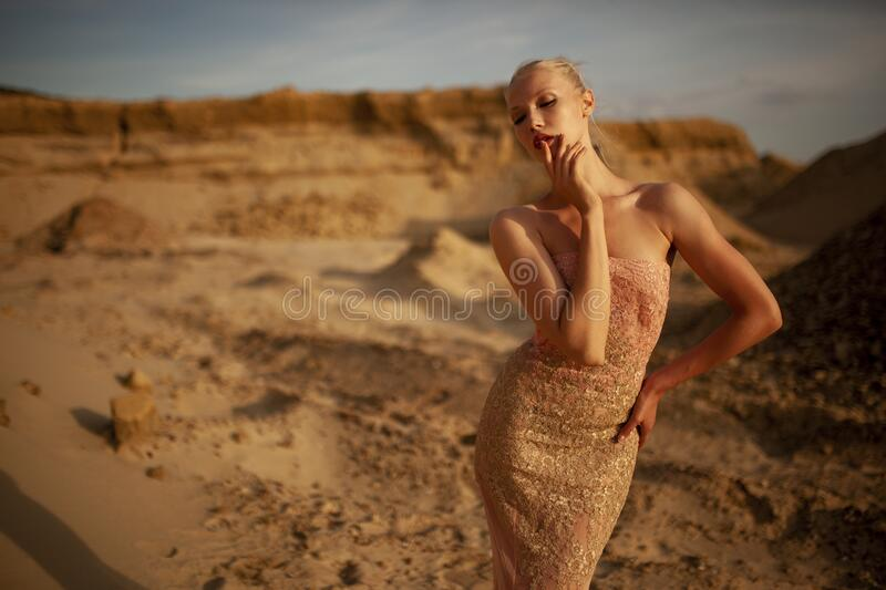 Closeup of a beauty frontal portrait of slim body young attractive and sexy woman in the desert in long gold dress. stock images