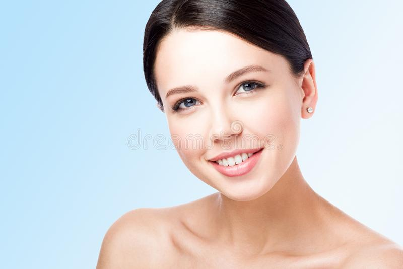 Closeup beauty portrait of young woman with beautiful smile. Neutral blue royalty free stock images
