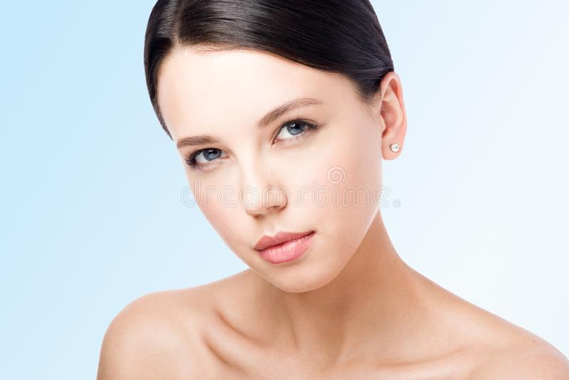 Closeup beauty portrait of young woman with sensual look. Isolated on blue royalty free stock photography