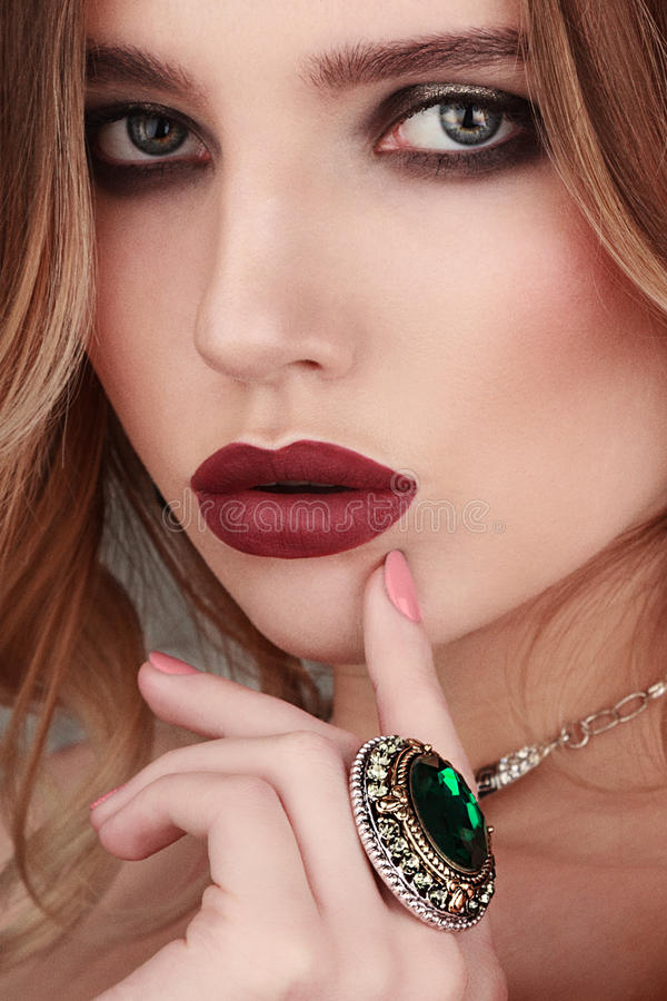 Closeup beauty portrait of young woman wearing ring with green g stock photo