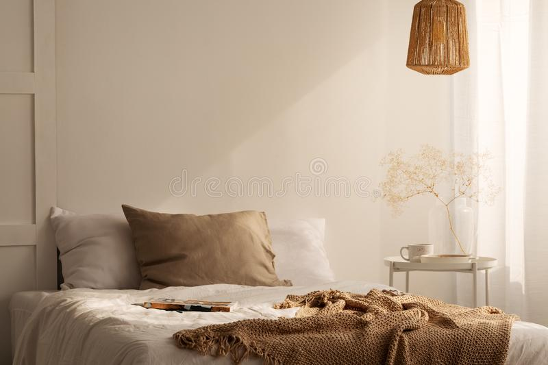 Closeup of bed with beige blanket and linen pillow in minimal bedroom interior, real photo. With copy space on the empty wall stock images