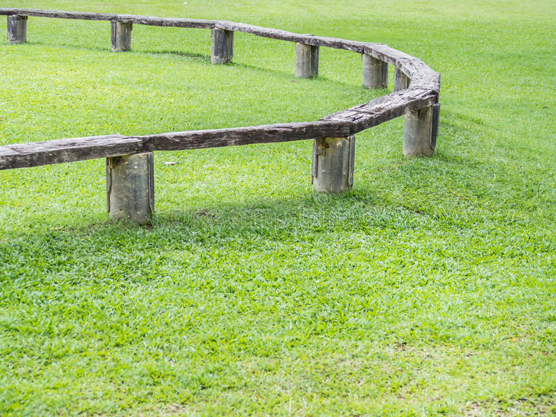Closeup of bench and green grass.  stock image