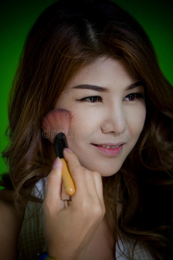 Closeup Beutiful model enjoy makeup applies brusher on her face. royalty free stock photography