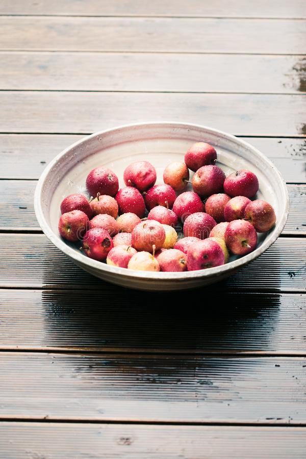 Closeup of big bowl of fresh red apples sprinkled raindrops on wooden table. Wet floor royalty free stock image