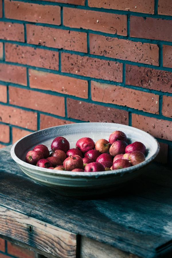 Closeup of big bowl of fresh red apples sprinkled raindrops on wooden table. Red color stock image