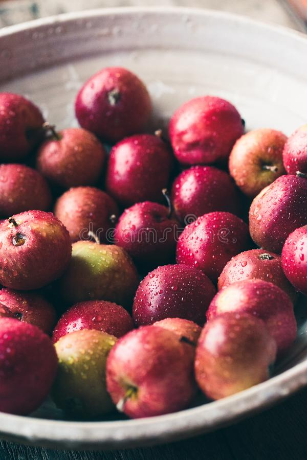Closeup of big bowl of fresh red apples sprinkled raindrops on wooden table. Red color stock photography