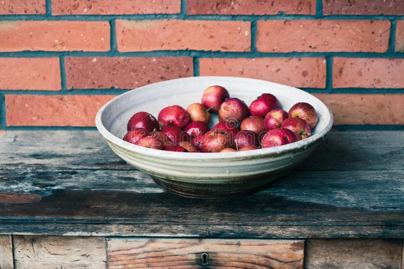 Closeup of big bowl of fresh red apples sprinkled raindrops on wooden table. Red color royalty free stock photography