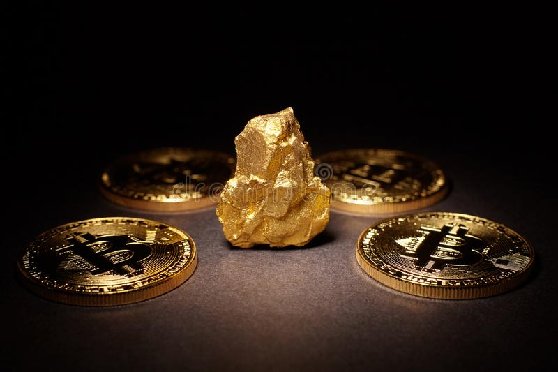 Closeup of big gold nugget and Gold Bitcoins Coins on black back royalty free stock image