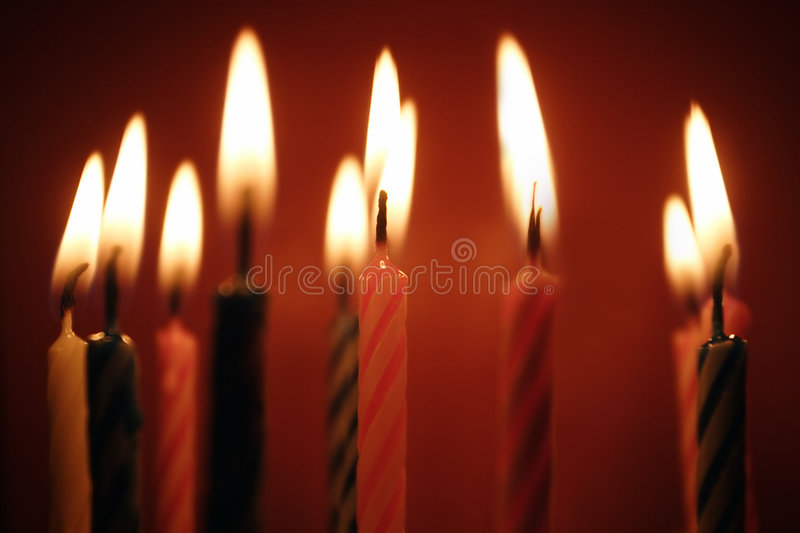 Closeup of birthday candles all lit. stock photos