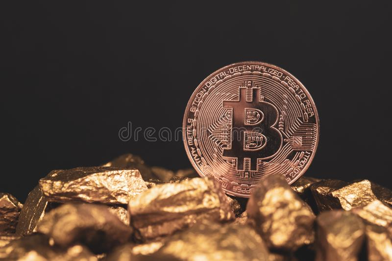 Closeup of bitcoin digital currency and gold nugget or gold ore on black background, precious stone or lump of golden stone, stock photo