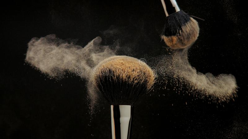 Closeup of black brush with a facial powder on it. And another brush whisk away a part of powder royalty free stock photos
