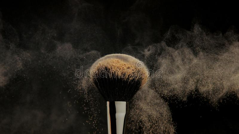 Closeup of black brush with a facial powder on it. And blowing out by wind stock photography