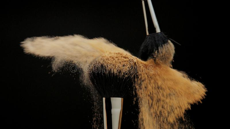 Closeup of black brush with a facial powder on it. And another brush whisk away a part of powder stock photography