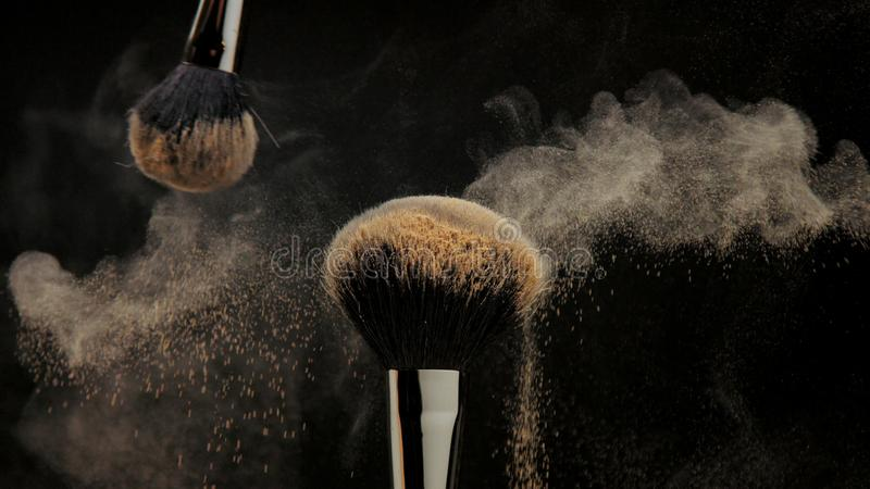 Closeup of black brush with a facial powder on it. And another brush whisk away a part of powder royalty free stock photography