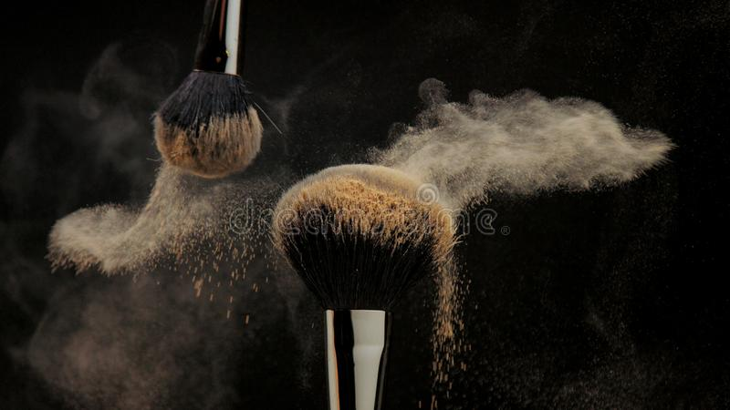 Closeup of black brush with a facial powder on it. And another brush whisk away a part of powder royalty free stock image