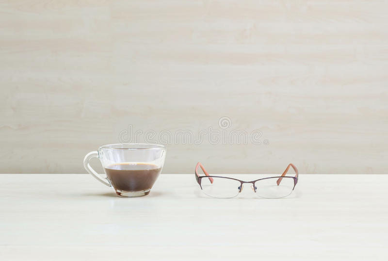 Closeup black coffee in transparent cup of coffee with eyeglasses on blurred wooden desk and wall textured background in the royalty free stock photo