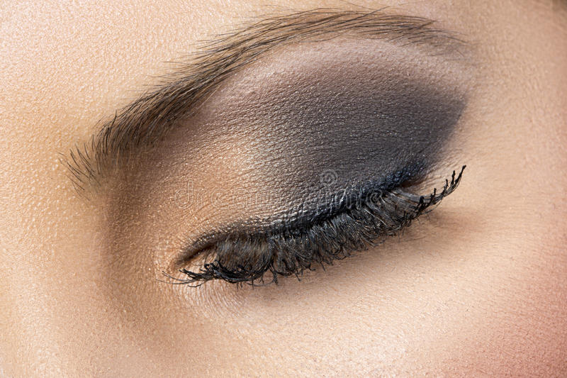 Closeup of black and gold smokey eye. A closeup of a beautiful woman's eyes with black and gold eyeshadow and long flowing eye lashes stock photos