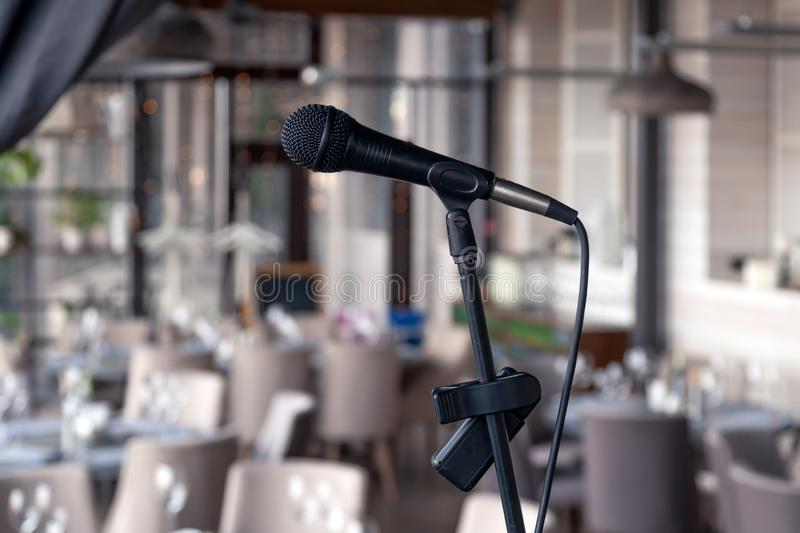 Closeup black iron microphone stands on stage background of restaurant hall served for banquet. Concept live music concert bar in royalty free stock image