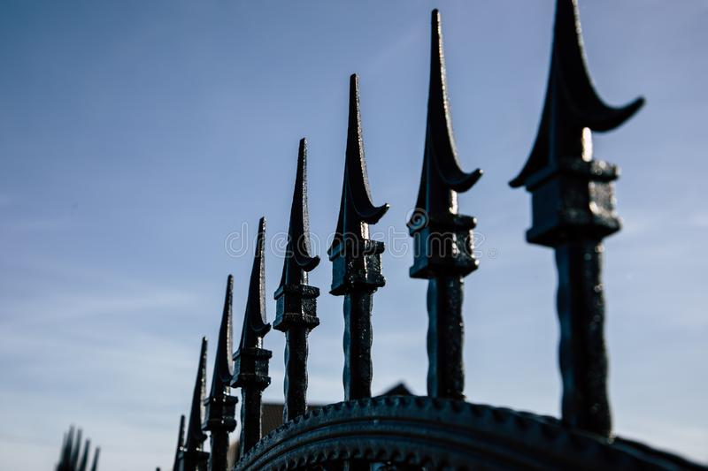 Closeup of black metal fence spikes perspective stock photo