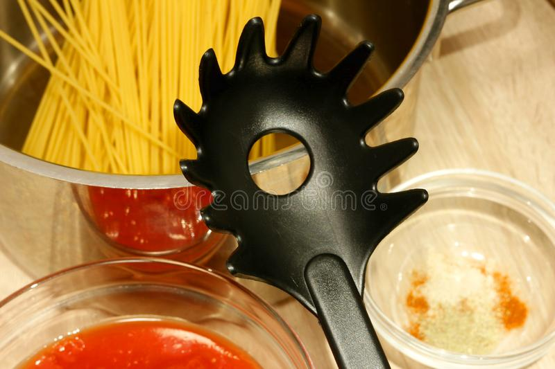 Plastic spaghetti server lies on the edge of a metallic saucepan filled with uncooked spaghetti straws stock images