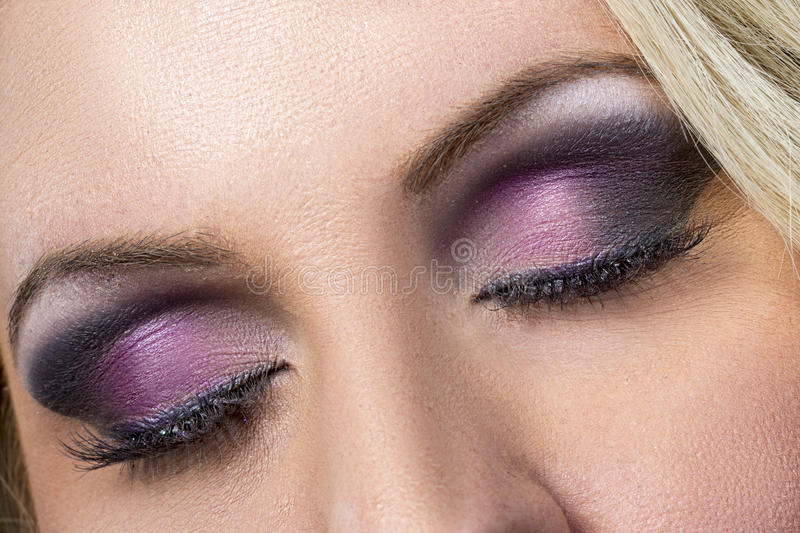 Closeup of black and purple smokey eye. A closeup of a beautiful woman's eyes with black and purple eyeshadow and long flowing eye lashes royalty free stock photo