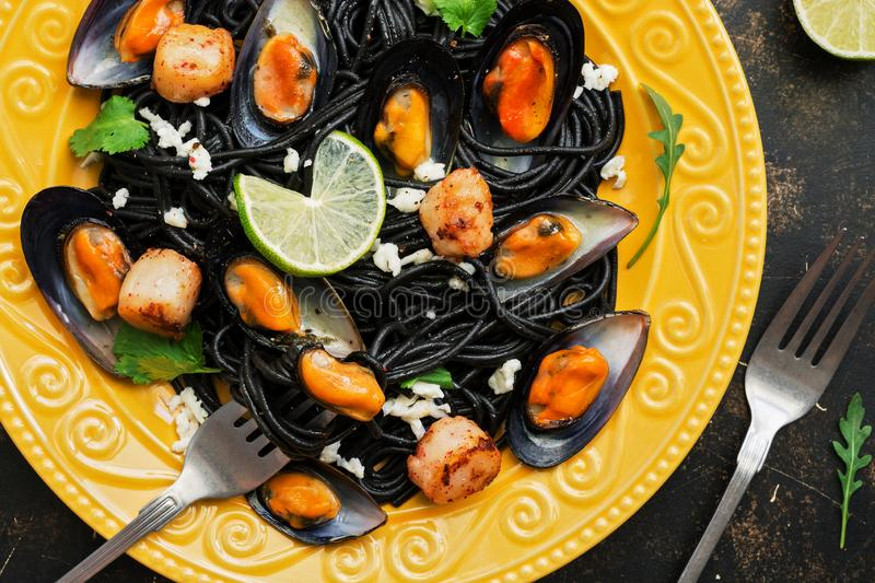 Closeup of black spaghetti with mussels, scallops, lime, mozzarella cheese and spices on a yellow plate. Top view stock images