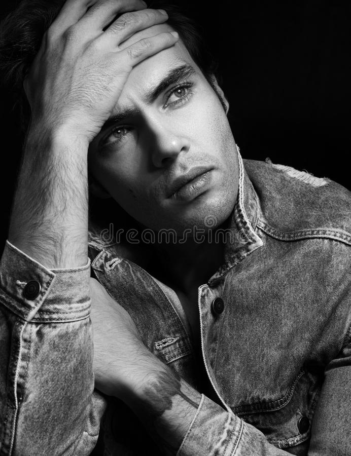 Closeup black and white portrait of pensive young man stock photo