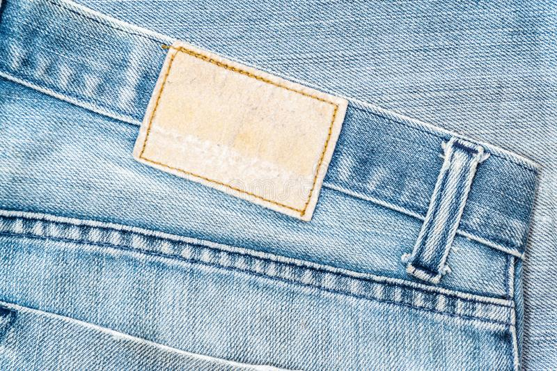 Closeup of blank grungy leather label on worn blue denim with orange seams stock images