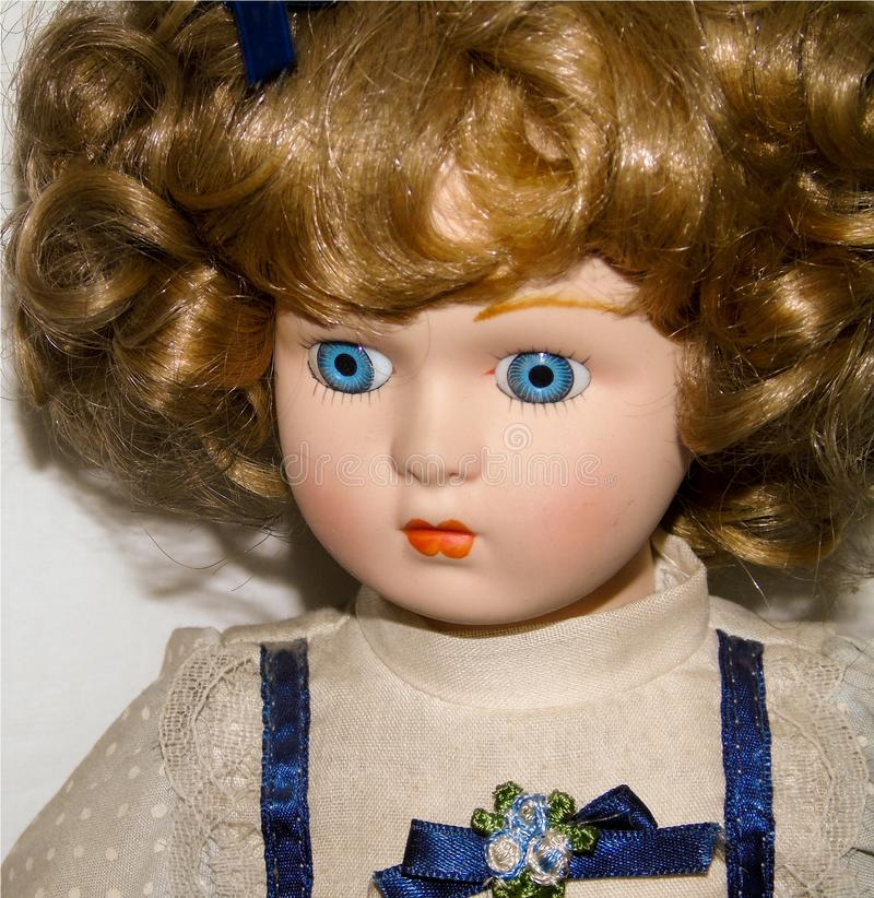 Closeup of a blonde porcelain doll on white background, vintage toys stock photo